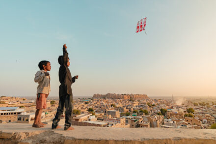 Boys playing with a kite with the Jaisalmer fortress in the background, India © Sandra Morante
