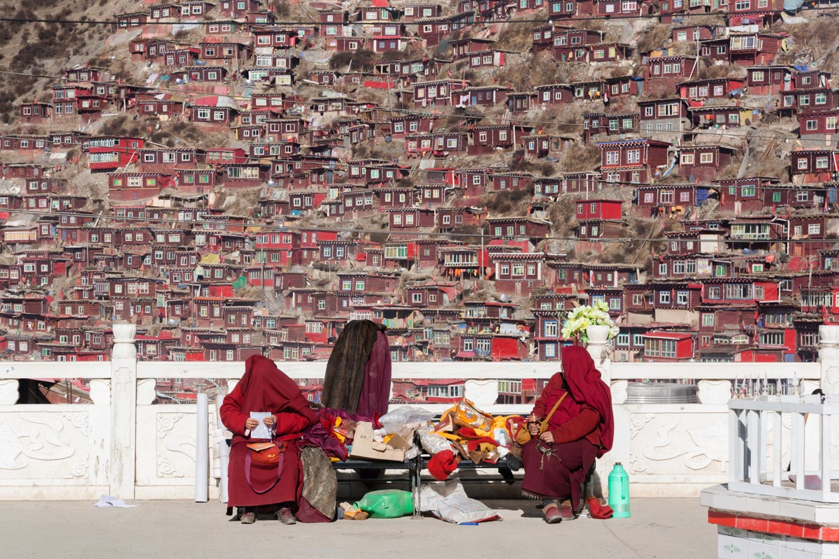 Two nuns protecting themselves from the harsh light, in Larung Gar, China