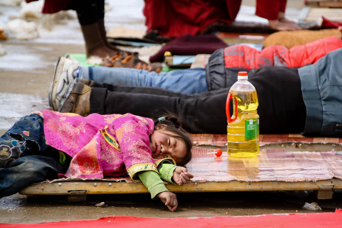 Bored little girl while her parents perform the Tibetan Buddhist prostrations in Larung Gar, China