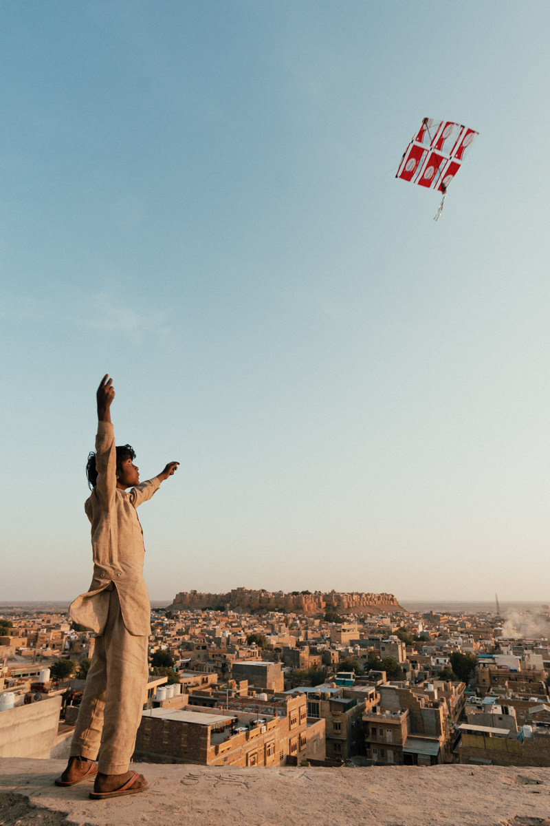 Boy playing with a kite with the Jaisalmer fortress in the background, India