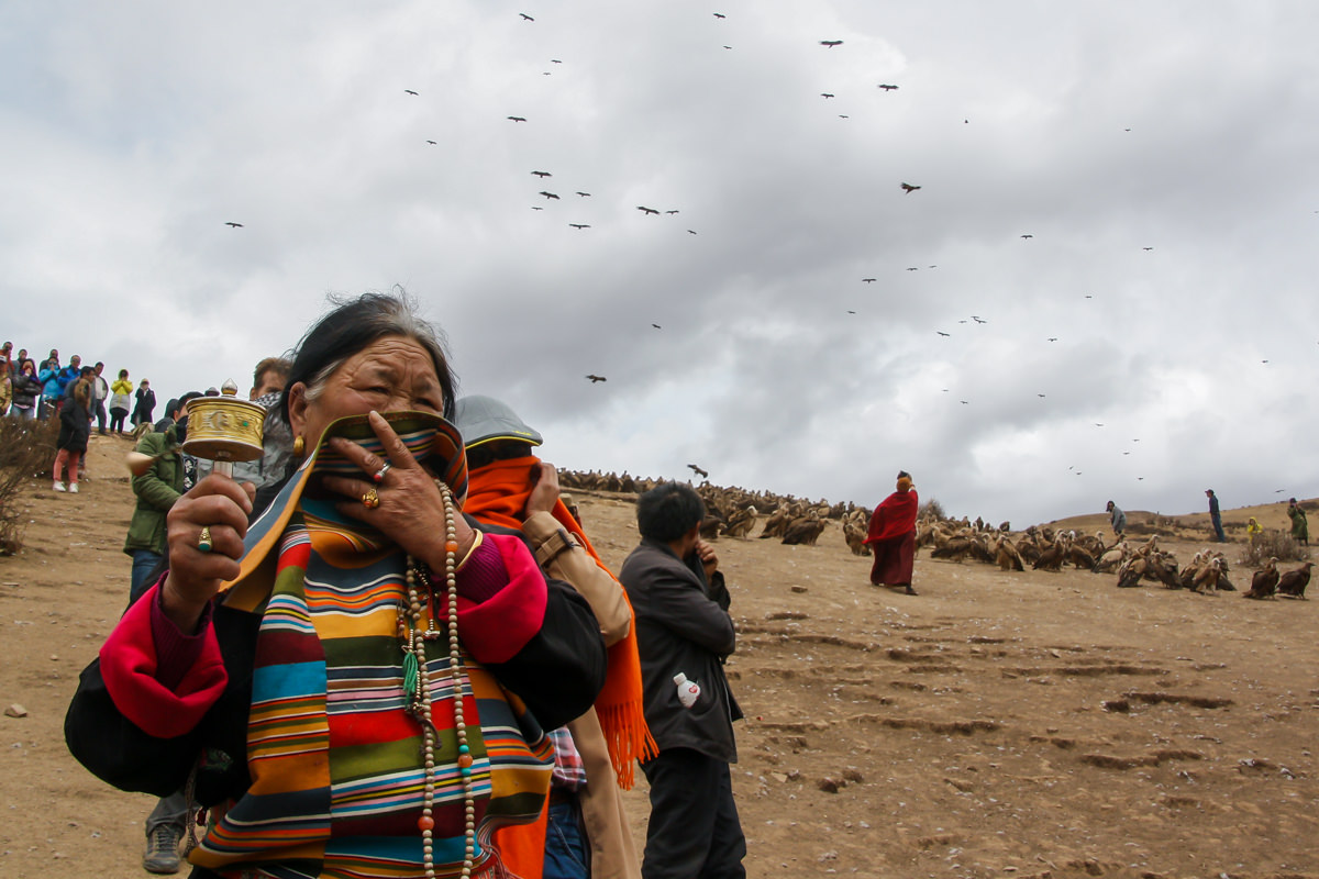 Tibetan woman spinning the prayer wheel during the ceremony of Sky Burial, in Larung Gar, China