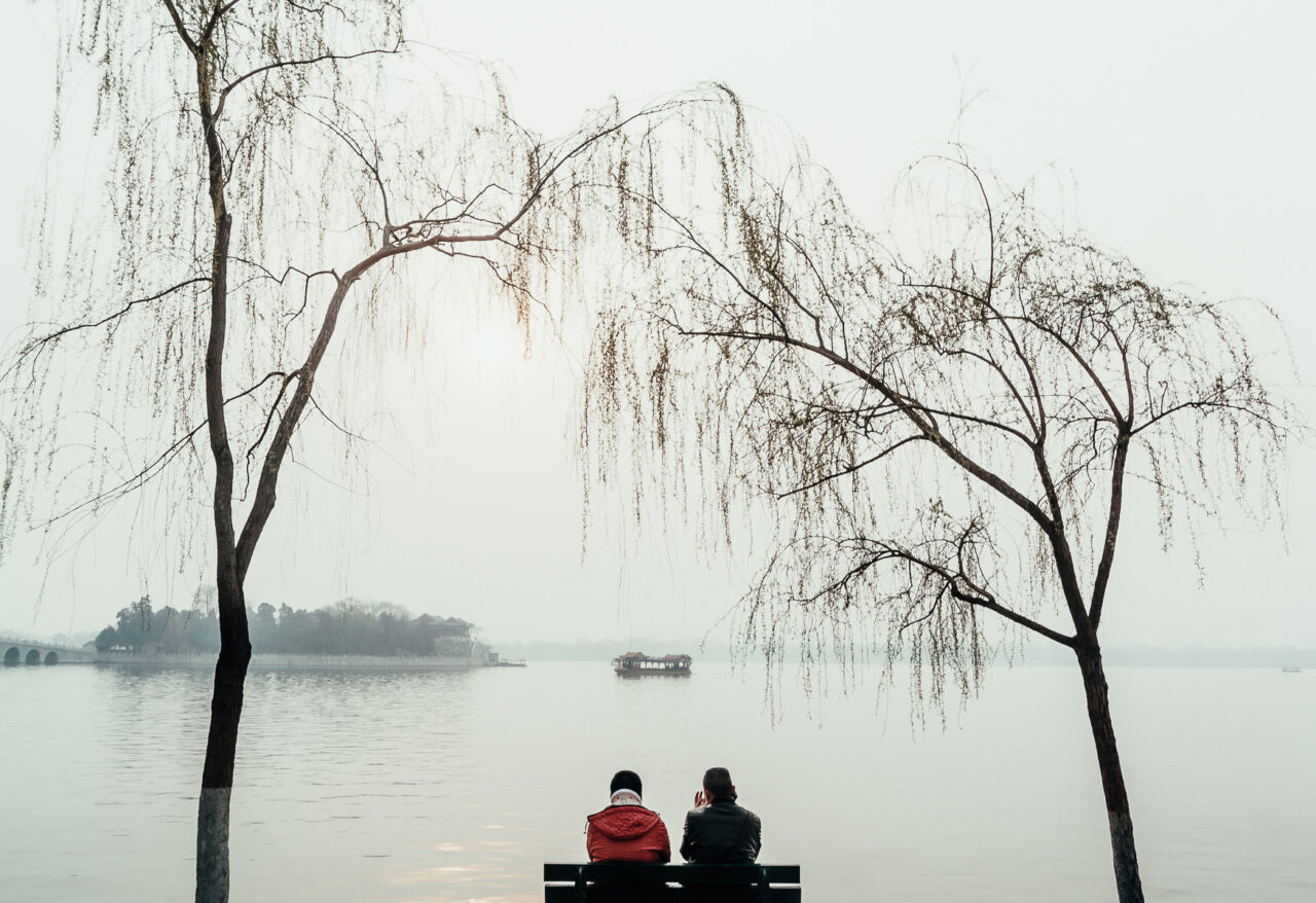 Couple resting in front of Houhai lake, in Beijing, China